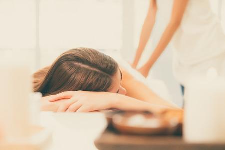 Femme détendue, massage du dos dans un spa de luxe avec massothérapeute professionnel en arrière-plan. Concept de bien-être, de guérison et de relaxation. Banque d'images