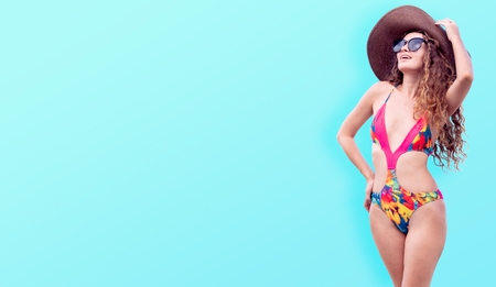Beautiful young sexy woman in swimsuit posing on color background. Summer advertising. Stock fotó
