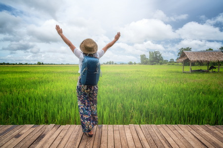 Woman traveller hiking in Asian rice field landscape. Backpacking vacation in spring season.