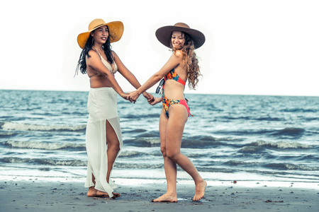 Happy women in bikinis dance together on tropical sand beach in summer vacation. Travel lifestyle.