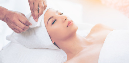 Relaxed young woman lying on spa bed prepared for facial treatment and massage in luxury spa resort. Wellness, stress relief and rejuvenation concept.