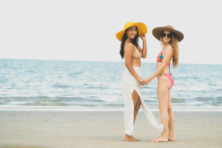 Happy women in bikinis go sunbathing together on tropical sand beach in summer vacation. Travel lifestyle.