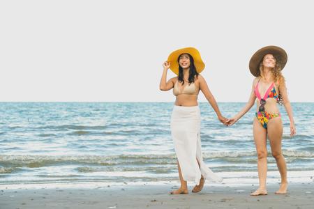 Mujeres felices en bikini van a tomar el sol juntas en la playa de arena tropical en las vacaciones de verano. Estilo de vida de viaje.