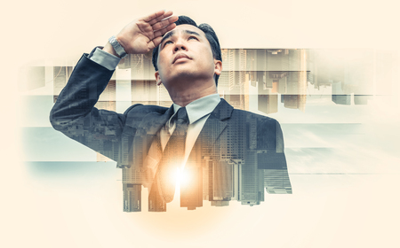 Double exposure - Business leader vision for success, looking away with modern buildings in city background. Concept of talented leadership.