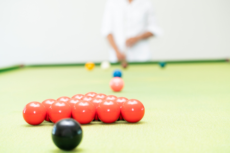 Young man playing snooker in the sport club.