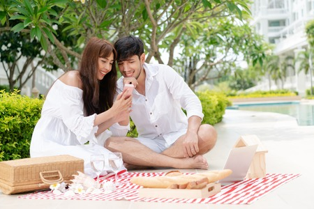 Happy young couple go picnic and dating at the park in summer. Stock Photo