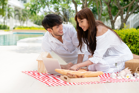 Happy young couple go picnic and dating at the park in summer. 写真素材