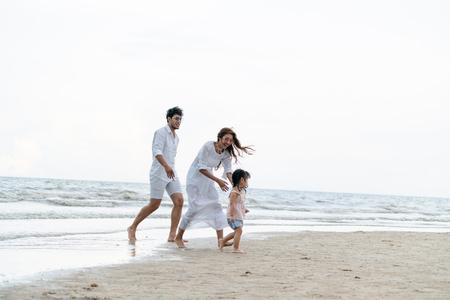 Heureuse famille de père, mère et enfants part en vacances sur une plage de sable tropicale en été. Banque d'images