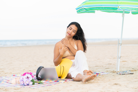 Plus size young woman sitting on tropical sand beach in summer. Holiday travel vacation. 免版税图像