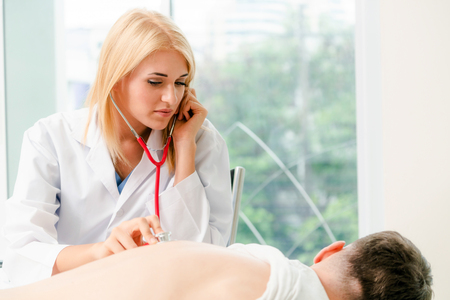 Woman doctor is examining male patient in hospital office. Healthcare and medical service. Stock Photo