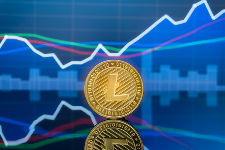 Litecoin (LTC) and cryptocurrency investing concept - Physical metal litecoin coins with global trading exchange market price chart in the background.