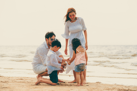 Happy family of father, mother and kids goes vacation on a tropical sand beach in summer. Stock Photo