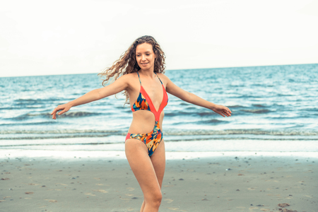 Happy young woman wearing swimsuit having good time at tropical beach in summer for holiday travel vacation.