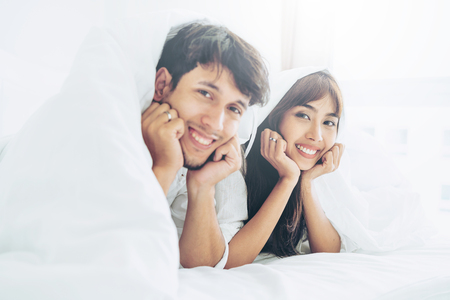Happy young couple relaxing in home bedroom after waking up in the morning.