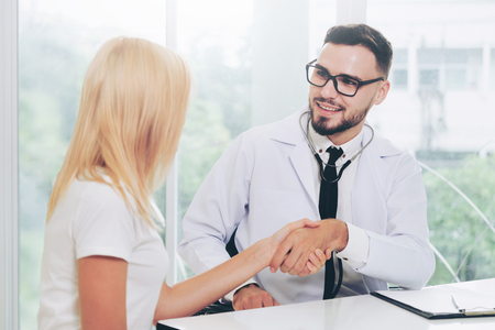 Male doctor doing handshake with female patient in hospital office. Healthcare and medical service.