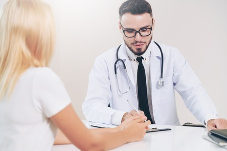 Male doctor is talking to female patient in hospital office. Healthcare and medical service. 版權商用圖片
