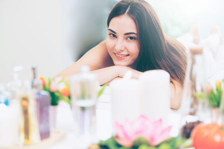 Relaxed woman lying on spa bed for aromatherapy massage in luxury spa with blurred foreground of spa treatment set including aromatic oil, candle and herbal scrub. Wellness and healing concept.