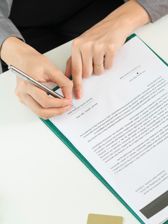 Businesswoman signs agreement contract at the office. Close up shot at the woman's hand. Concept of business partnership and legal activities of lawyer. Stockfoto