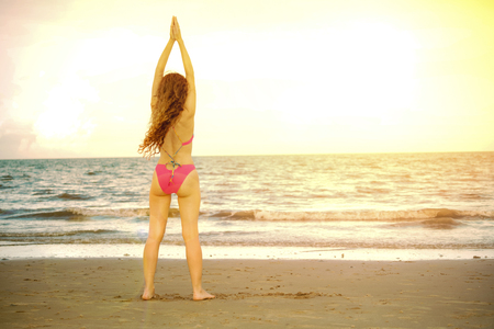 Young woman practicing yoga pose on the beach in summer. Healthy lifestyle and meditation. 스톡 콘텐츠