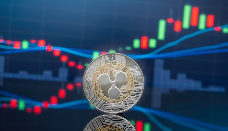 Ripple (XRP) and cryptocurrency investing concept - Physical metal Ripple coins with global trading exchange market price chart in the background. Stock Photo