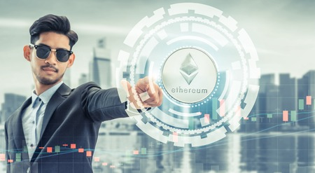 Ethereum and cryptocurrency investing concept - Businessman pointing at Ethereum coin (ETH) with modern business building and cityscape in the background. Blockchain technology. Zdjęcie Seryjne