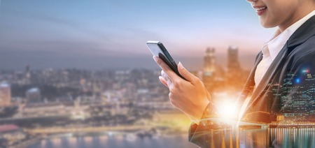 Joven empresaria mediante teléfono móvil con fondo de edificios de la ciudad moderna. Futuro concepto de tecnología de telecomunicaciones e internet de las cosas (IOT).