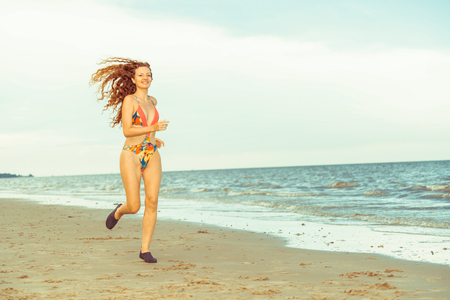 Attractive woman runner runs on tropical sand beach in summer. Healthy lifestyle and running sport concept. Archivio Fotografico