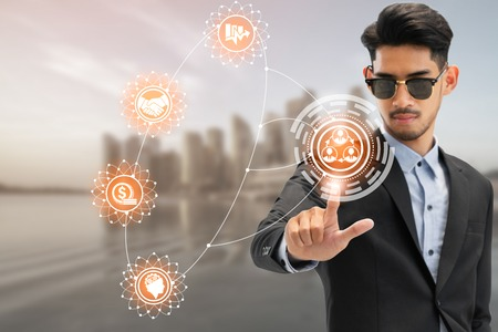 Businessman using future graphic interface application with modern business buildings and cityscape in the background. Digital innovation and technology disruption concept.