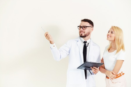 Male doctor points pen at empty copy space while standing beside female patient.