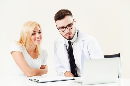 Male doctor talks to female patient in hospital office while looking at the patients health data on laptop computer on the table. Healthcare and medical service. 版權商用圖片
