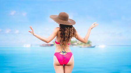 Glückliche junge Frau, die Badeanzug am tropischen Sandstrandresort im Sommer für Urlaubsreiseurlaub trägt. Standard-Bild