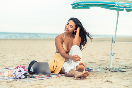 Plus size young woman sitting on tropical sand beach in summer. Holiday travel vacation. Фото со стока