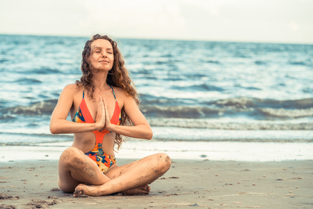 Young woman practicing yoga pose on the beach in summer. Healthy lifestyle and meditation. Stock Photo