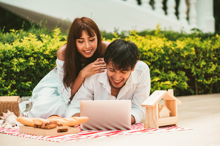 Happy young couple go picnic and dating at the park in summer. 版權商用圖片