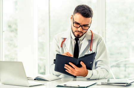 Doctor reading while writing note on a book at office in the hospital. Medical and healthcare concept.