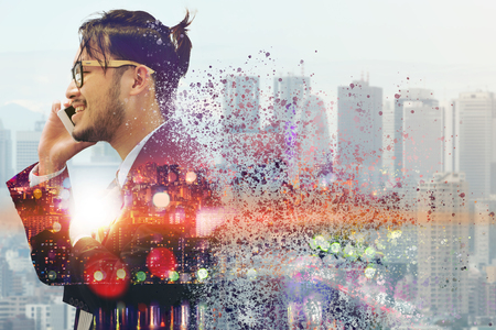 Surreal Image of Communication Concept - Young businessman using mobile phone with modern city buildings background. Future innovation technology and internet of things ( IOT ). Stock Photo