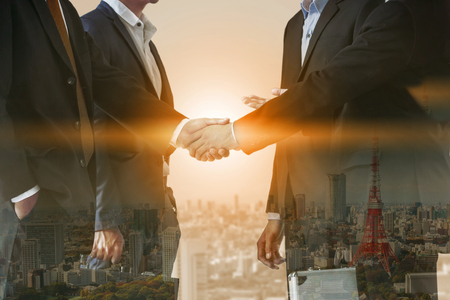 Accord de poignée de main de gens d'affaires à double exposition avec paysage urbain en arrière-plan. Réunion et collaboration des dirigeants d'entreprise.