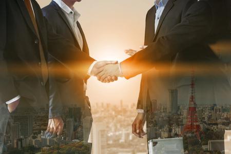 Acuerdo de apretón de manos de gente de negocios de doble exposición con paisaje de fondo. Reunión y colaboración ejecutiva empresarial.