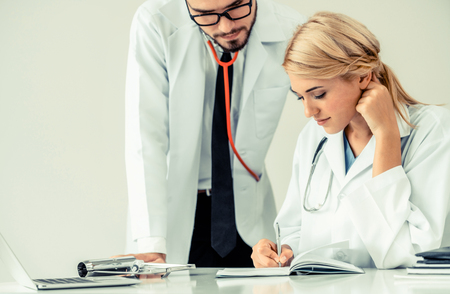 Doctor at hospital office writes notes on patients report while having conversation with another doctor that standing beside her.