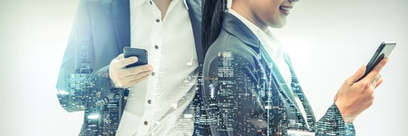 Young business people using mobile phone with modern city buildings background. Future telecommunication technology and internet of things ( IOT ) concept.