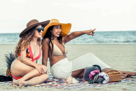 Happy women in bikinis sitting together on tropical sand beach in summer vacation. Travel lifestyle.