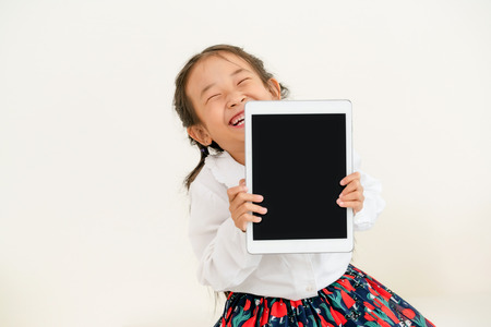 Little kid showing black screen of tablet computer on white background. Stock Photo