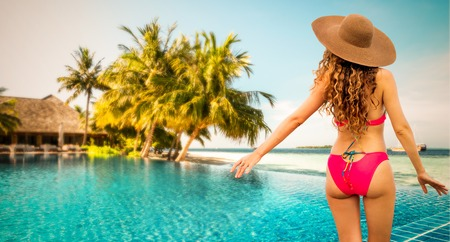 Happy young woman wearing swimsuit at tropical sand beach resort in summer for holiday travel vacation. Standard-Bild