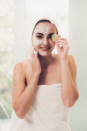 Beautiful woman having a facial mask treatment with cucumber cream extract showing benefit of nature treatment. Anti-aging, facial skin care and luxury lifestyle concept.