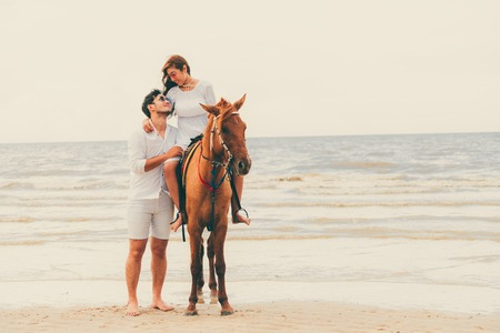Young couple goes honeymoon horse riding on the beach in summer vacation. Foto de archivo
