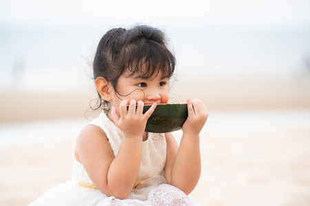 Adorable kid eating watermelon on the tropical sand beach in summer. Stock Photo