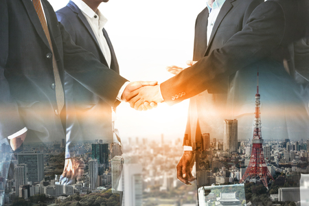 Double exposure business people handshake agreement with cityscape in background. Business executive meeting and collaboration.