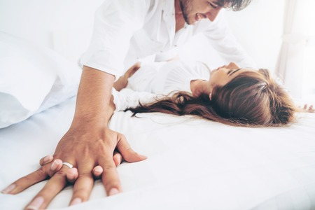 Romantic love of intimate young couple in home bedroom foreplay in the bed.