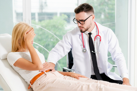 Male doctor is talking and examining female patient in hospital office.
