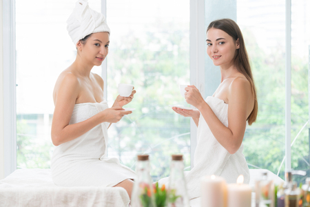 Two women drinking tea or herbal drinks while having conversation in luxury day spa. Wellness, leisure and healthcare concept.